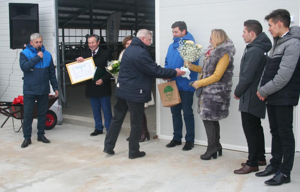 Bogdan Godlewski i Wiesław Bogucki wręczają pamiątkowy dyplom i upominek. Otwarcie obory u Państwa Koc