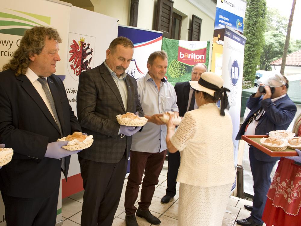 Mariusz Wykrzykowski, członek Zarządu SHiUZ (drugi od lewej) otrzymuje symboliczny bochen dożynkowy